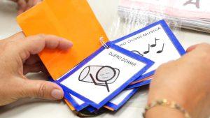 Professora manuseia o chaveiro de comunicação formado por cartões com figuras e dizeres como Quero dormir e Quero ouvir música