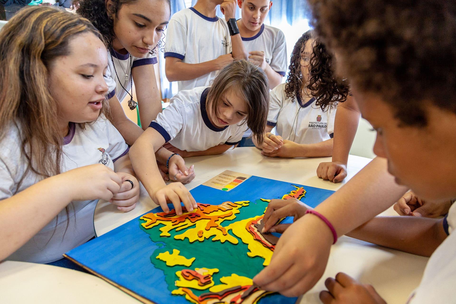 Em sala de aula, estudantes interagem com mapa tátil apoiado sobre mesas escolares. Uma das estudantes se debruça sobre a mesa para fixar uma das camadas de relevo do material. Fim da descrição.
