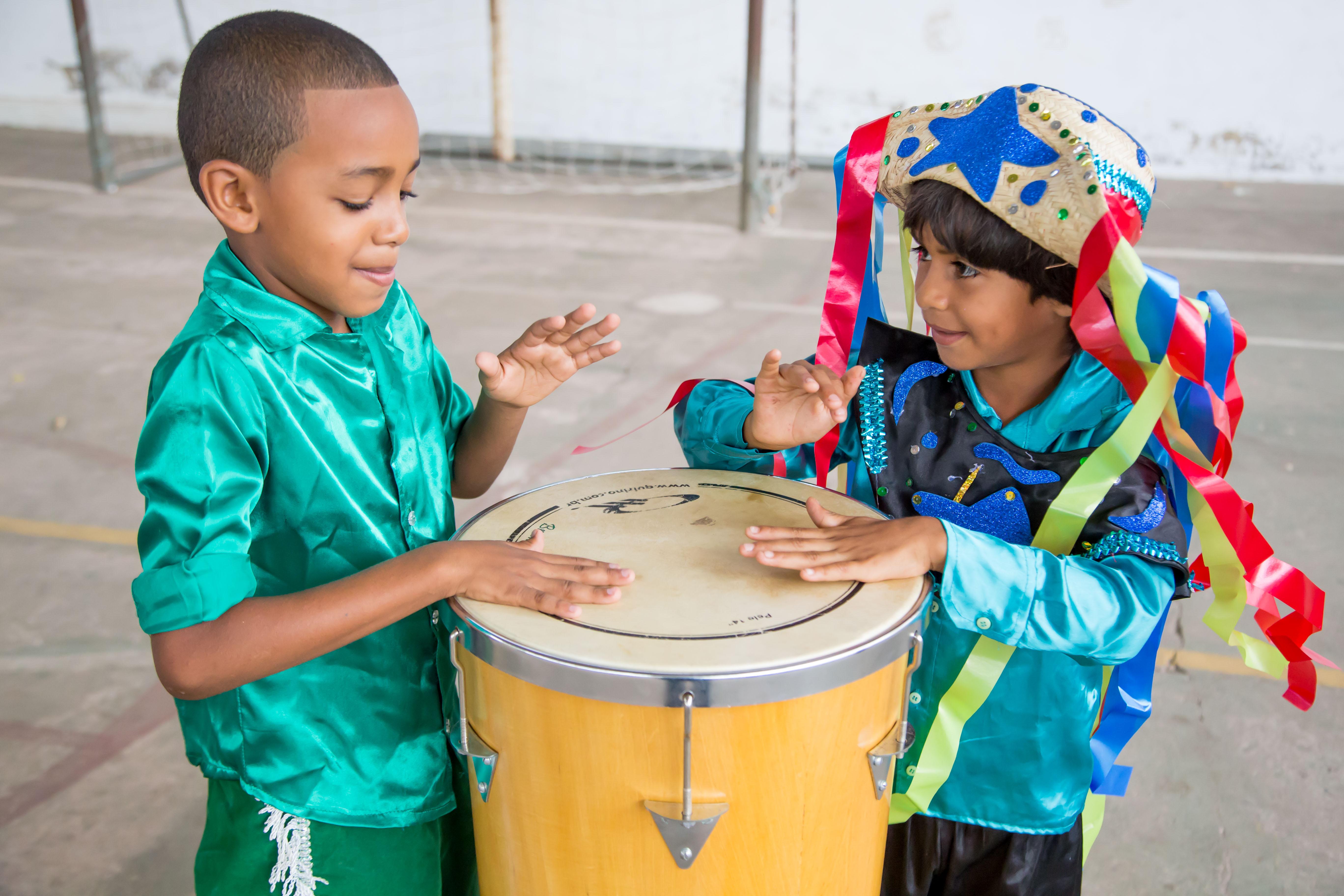 Dois garotos com roupas coloridas tocam uma timba.