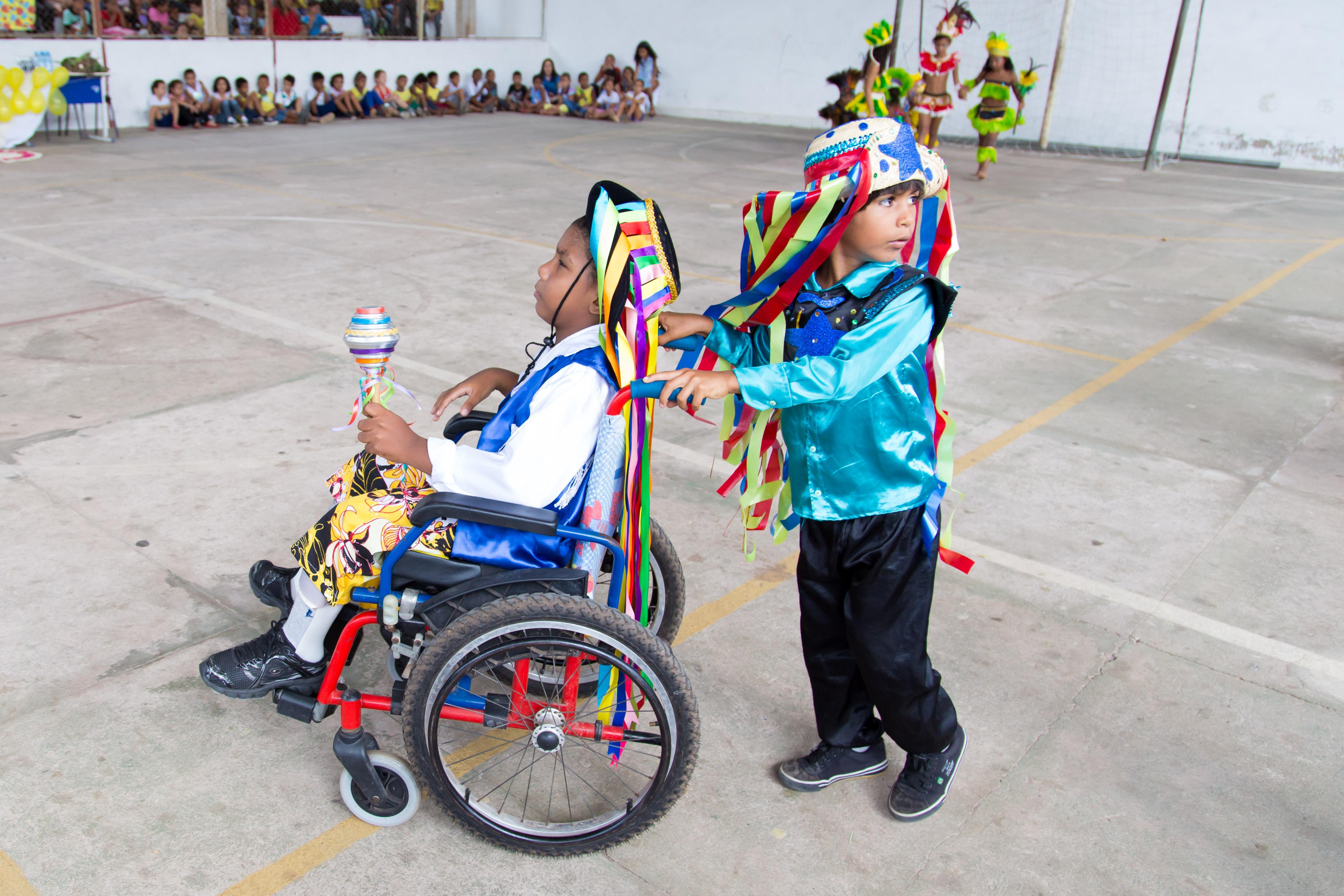 Dois garotos com roupas coloridas dançam. Um deles usa uma cadeira de rodas e o outro o empurra.