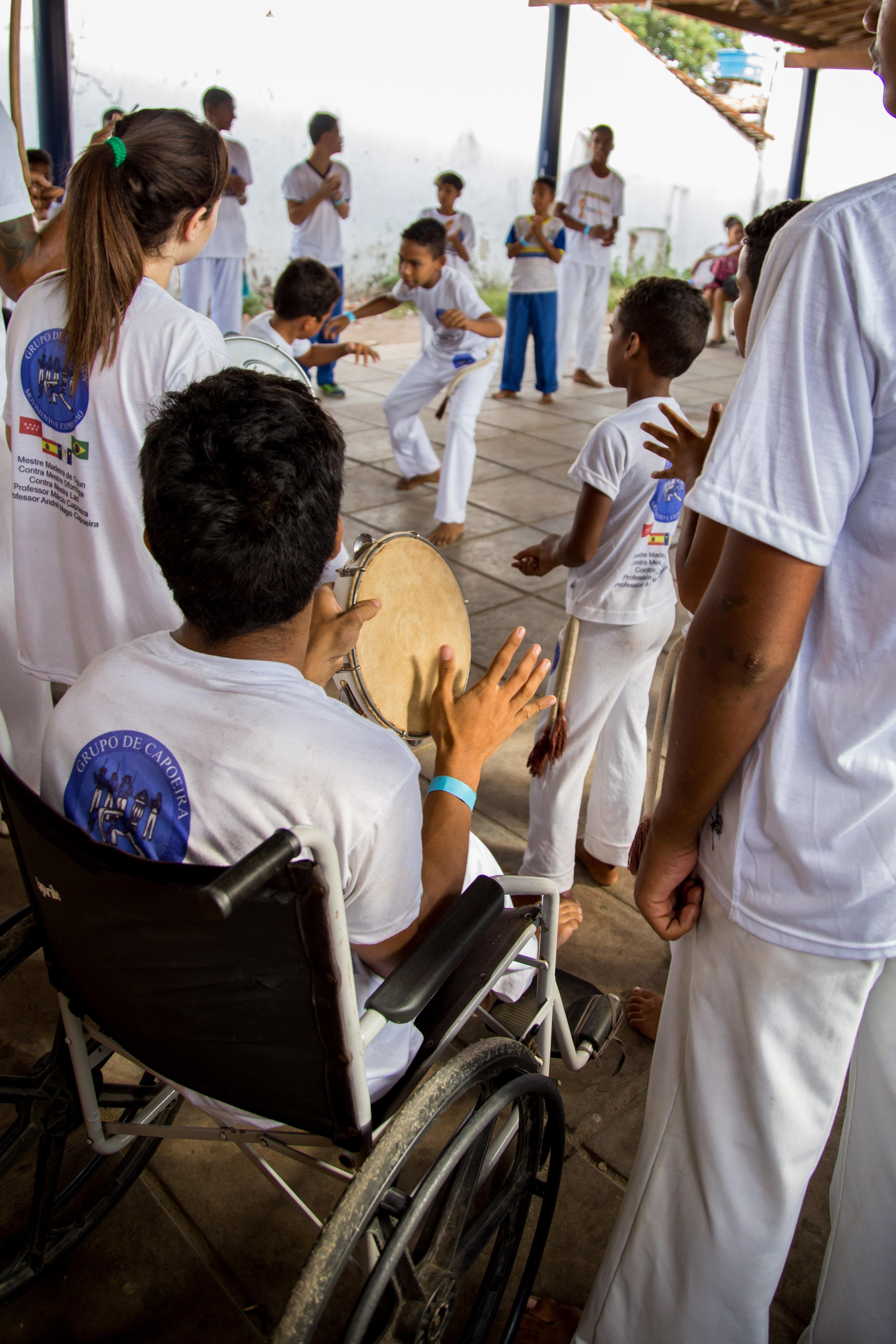 Um estudante com deficiência física está sentado em uma cadeira de rodas e é mostrado de perfil tocando um pandeiro. Ao seu redor, alunos jogam capoeira. Todos vestem roupas brancas.