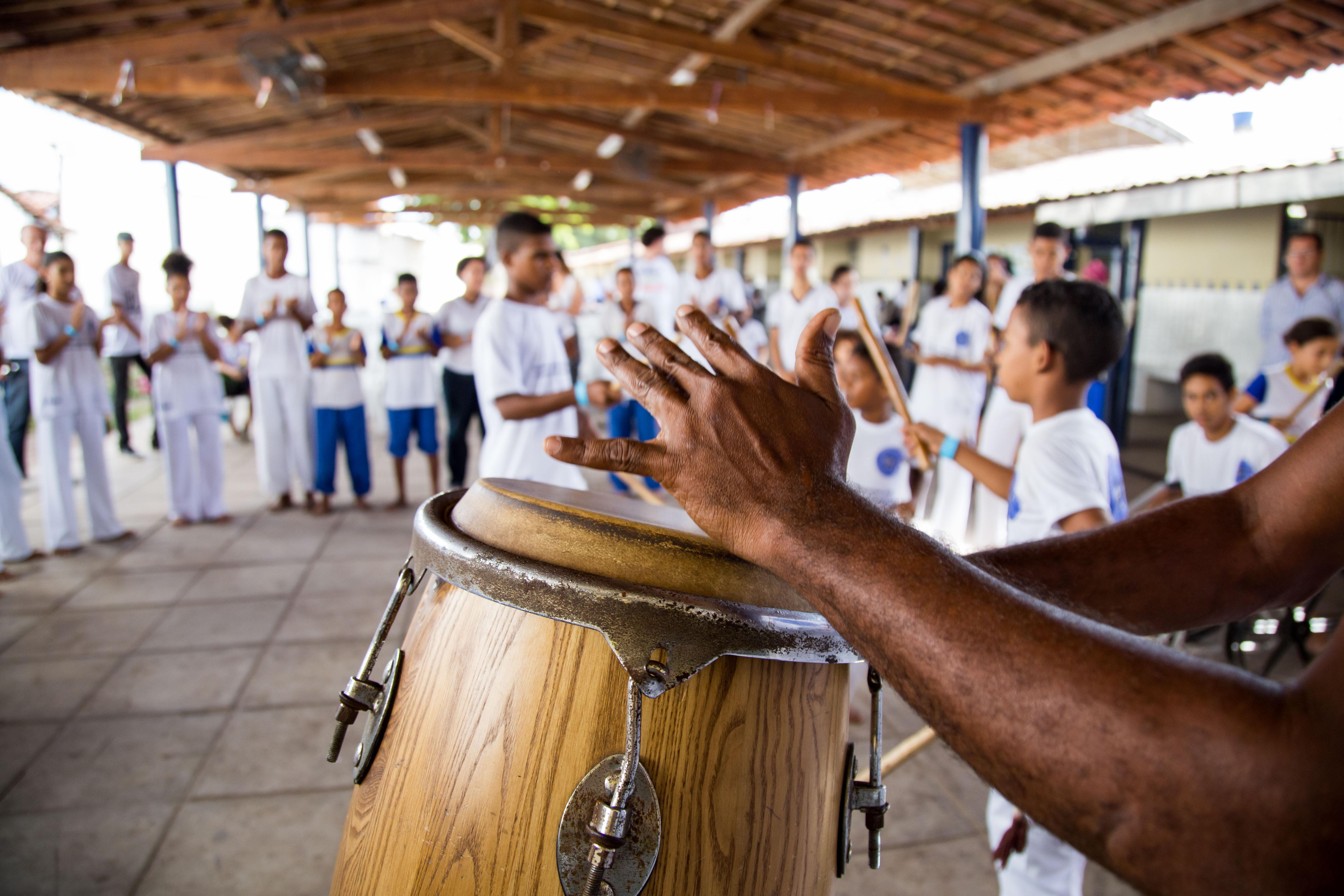 Mão toca o instrumento atabaque (tambor alto), enquanto crianças jogam capoeira ao fundo.