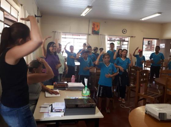 Sala de aula cheia de estudantes. Eles estão com uma das mãos sobre a cabeça, imitando o gesto das professoras a frente.