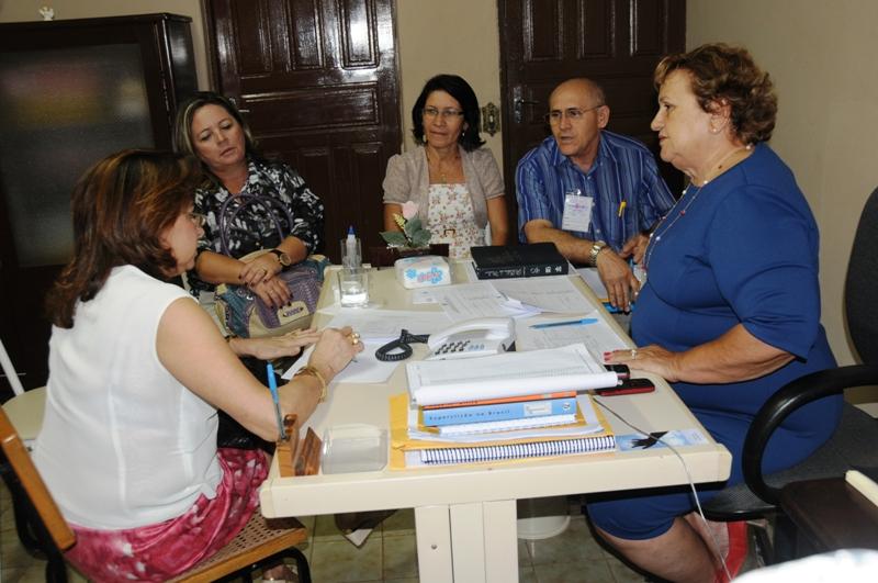Grupo de 5 adultos conversa ao redor de uma mesa repleta de papéis e materiais de escritório.