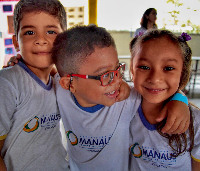 Três alunos sorridentes, com e sem deficiência, posam abraçados.