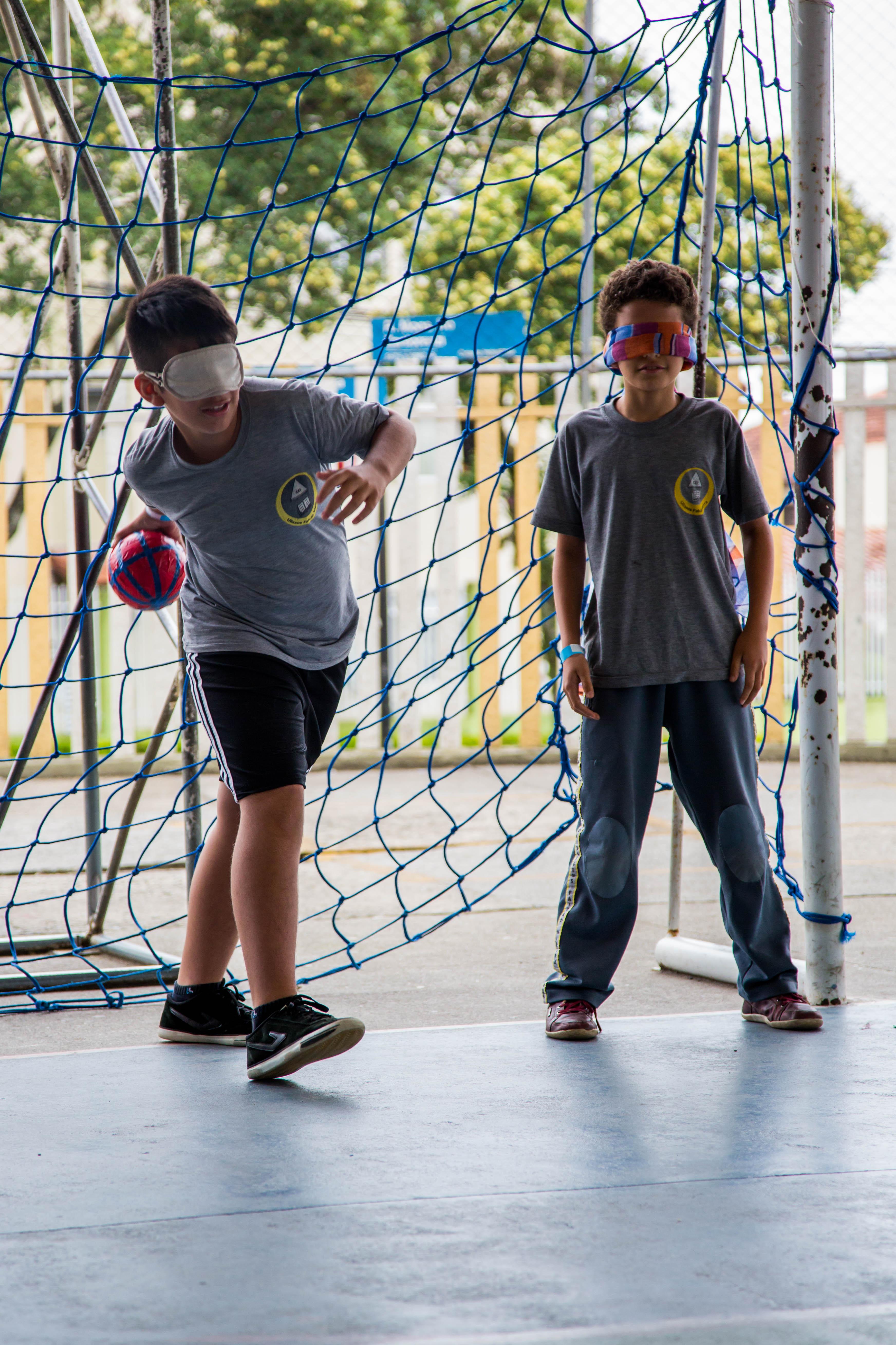 Dois meninos vestem uniformes escolares e têm os olhos vendados. Eles estão à frente de uma rede de gol em uma quadra esportiva. O garoto à esquerda segura uma bola de tamanho médio e faz movimento com o braço para arremessá-la.