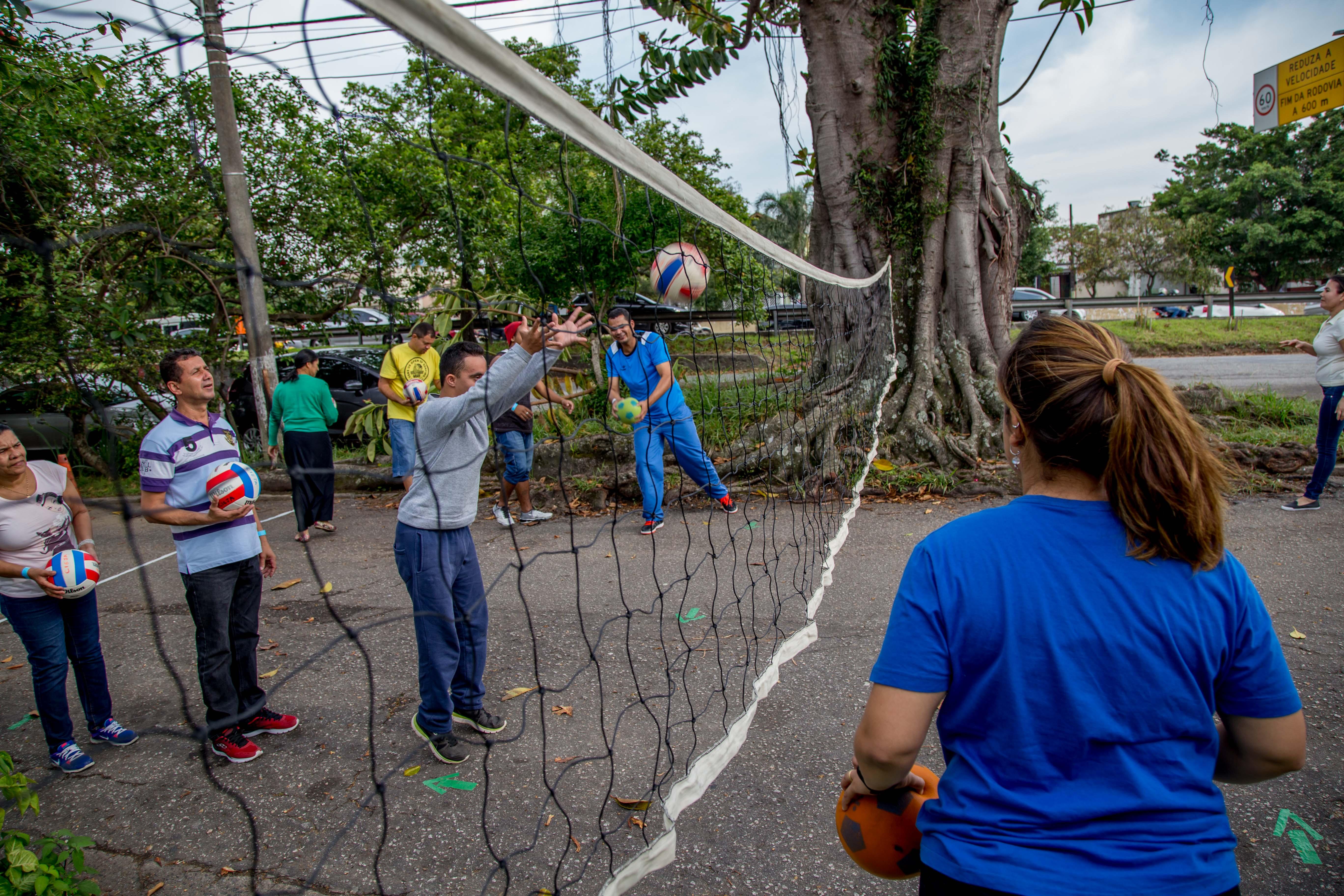 Estudante com deficiência lança bola acima de rede de vôlei pendurada a uma altura baixa na rua. Outros educandos e professores acompanham a atividade ao redor.