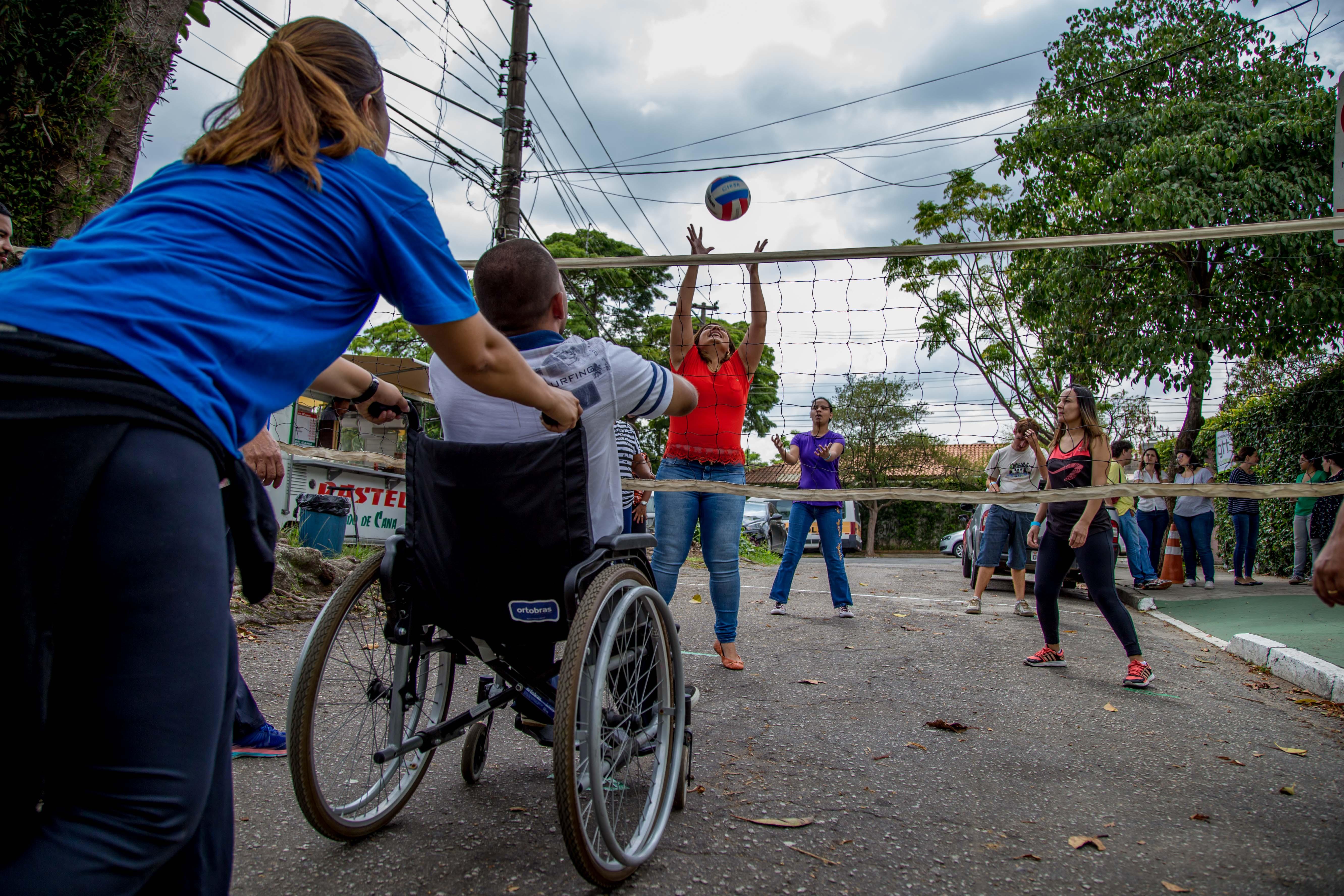 De costas para a imagem, professora empurra cadeira de rodas de aluno com deficiência física que espera recebimento de bola arremessada por outra estudante do lado oposto da rede pendurada na rua.