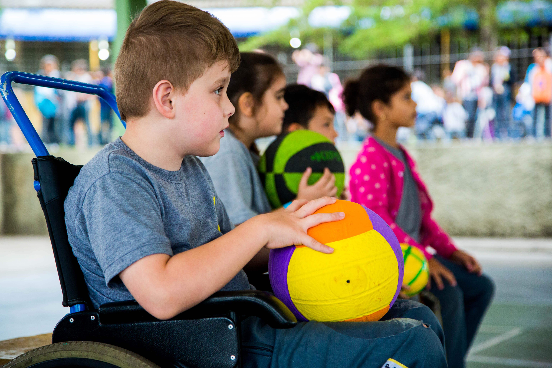 Descrições imagens: Em uma quadra esportiva de escola, um garoto de nove anos em uma cadeira de rodas segura uma bola de vôlei. Ao fundo, outros estudantes estão sentados em cadeiras