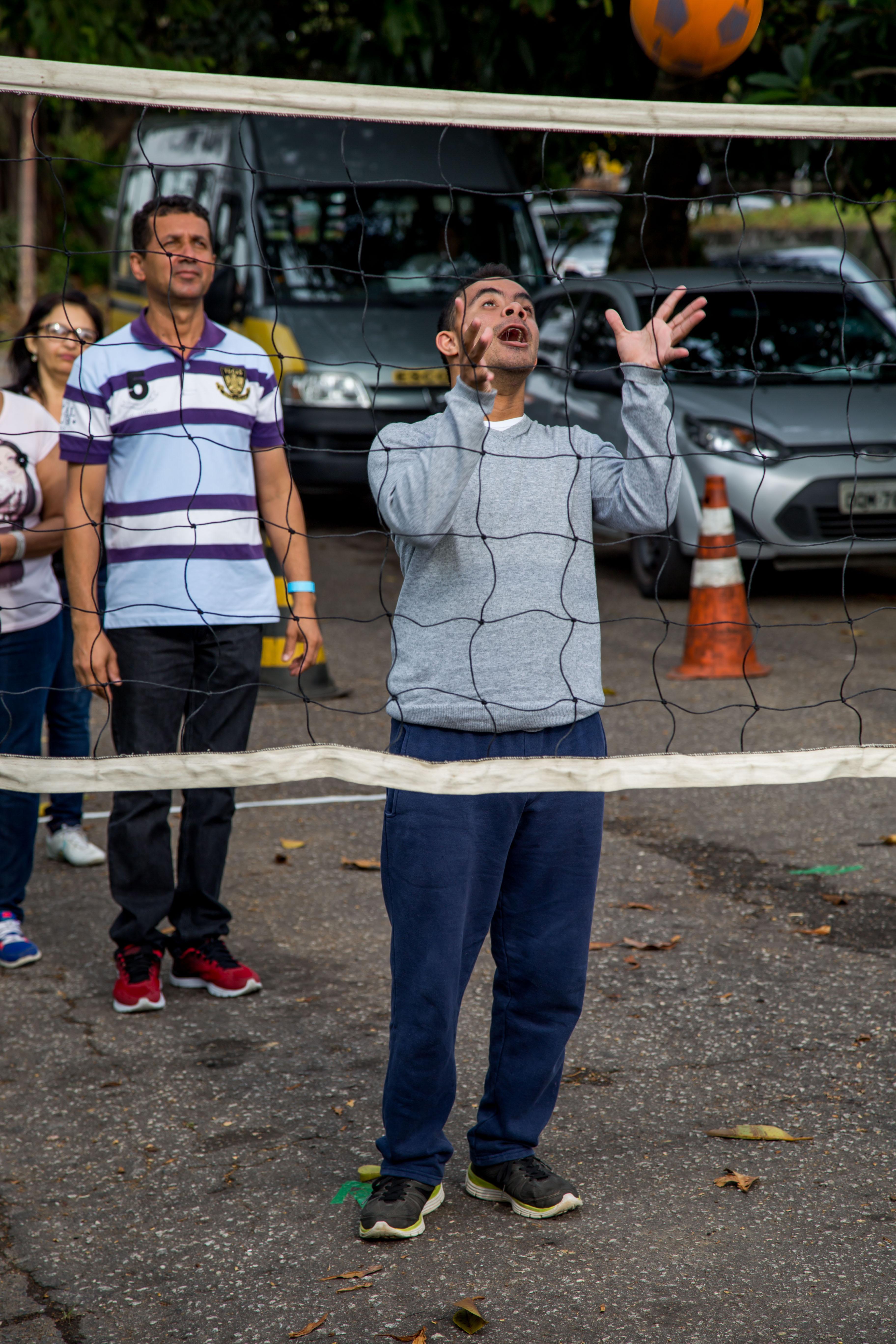 Estudante com deficiência lança bola para cima de rede de vôlei pendurada a uma altura baixa na rua. Ao redor, outros educandos e professores acompanham a atividade.