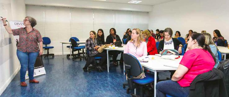 Participantes agrupados em mesas na sala de aula, sentados, observam à sua frente mulher anotando no quadro, em pé.