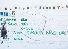 """Folha repleta de escritos feitos a mão por uma criança com lápis de cor verde. É possível ler palavras como """"Sapo"""", """"não lava porque não"""" e """"mora"""". Há diversas letras coladas no topo da folha."""