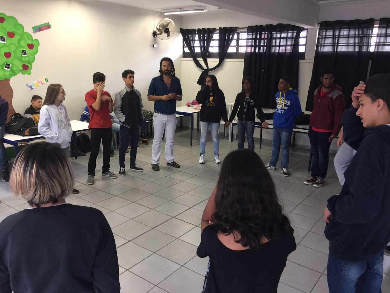 Estudantes conversam em sala de aula. Eles estão de pé, em um círculo.