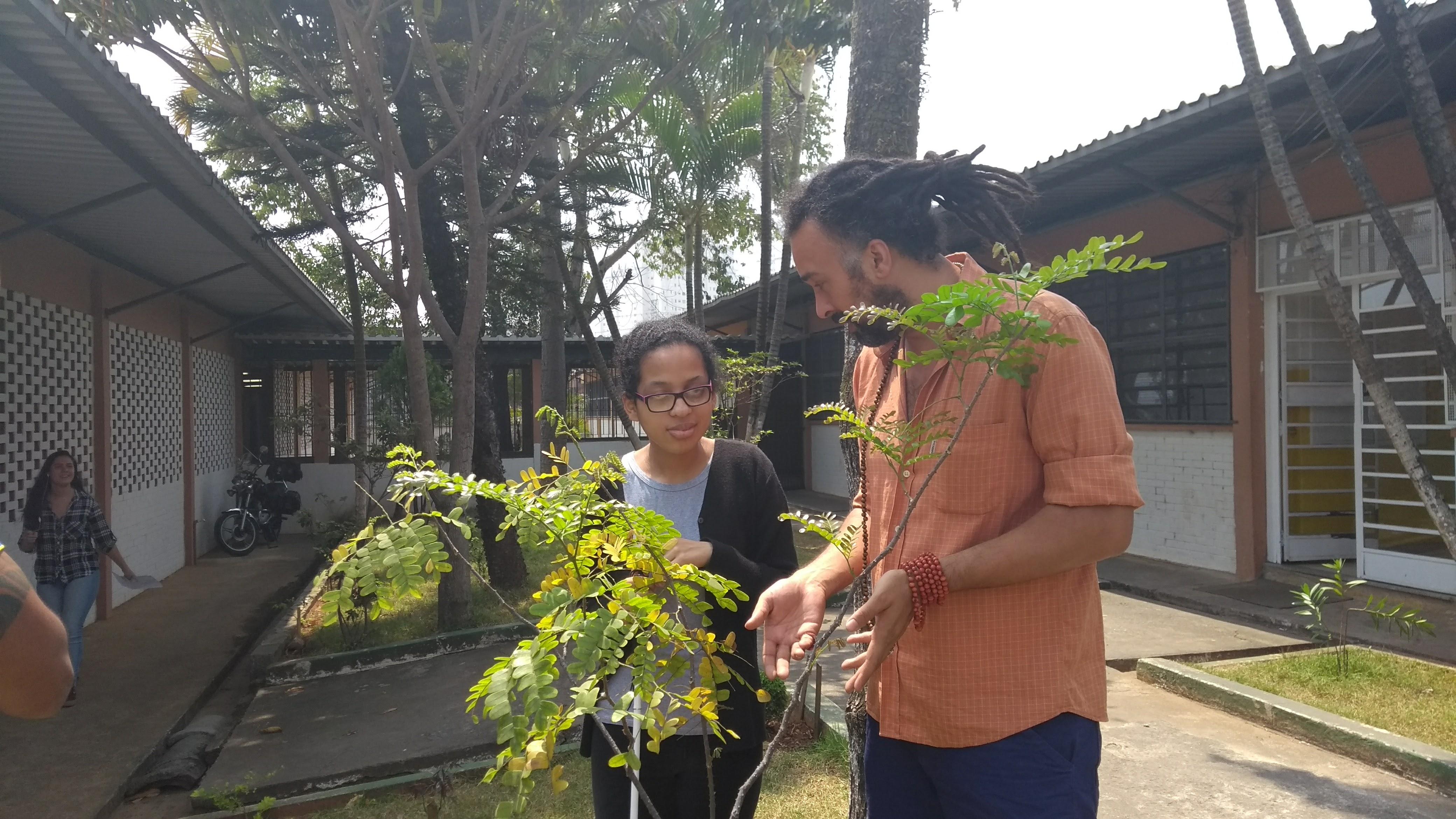 Professor orienta aluna a tocar em uma árvore no pátio da escola.
