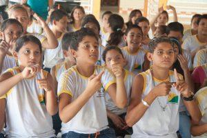 Um grupo de crianças com uniformes escolares faz sinais com as mãos durante aula de Libras