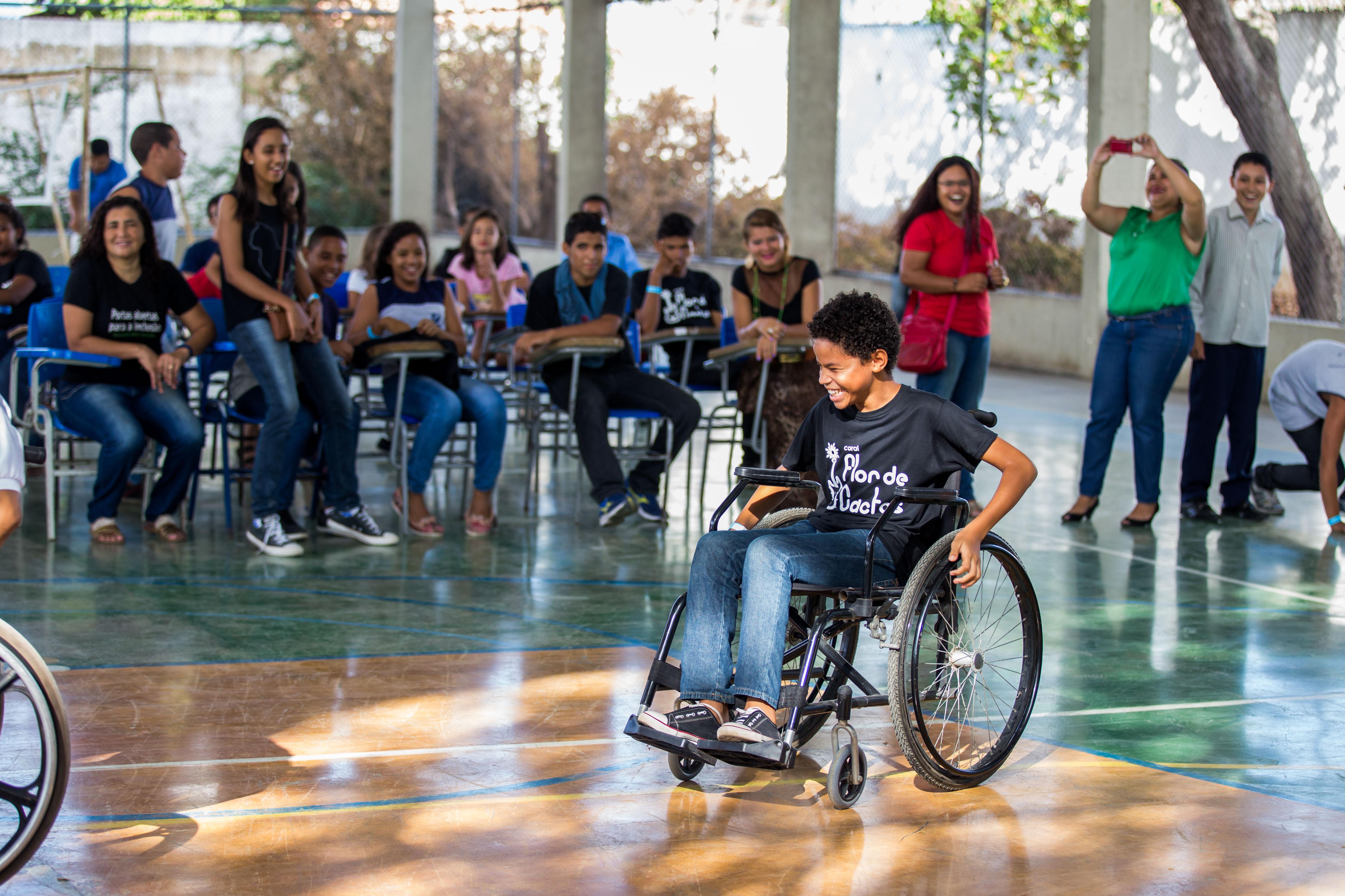 Diversos estudantes entre 10 e 15 anos estão sentados em cadeiras no centro de uma quadra escolar. Um garoto em uma cadeira de rodas se destaca no meio.