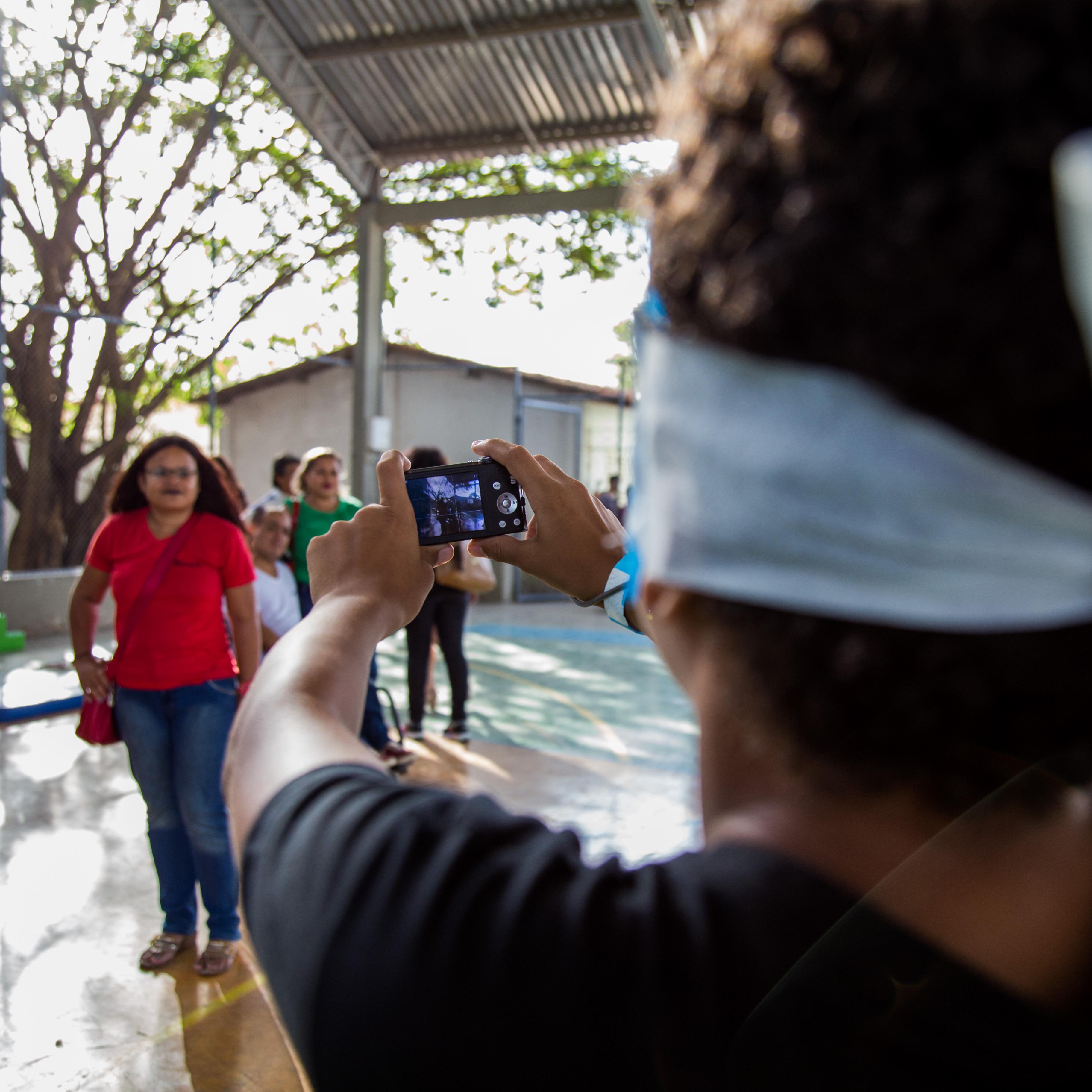 Um aluno vendado segura uma câmera fotográfica digital com as duas mãos. Mesmo sem enxergar, ele procura mirar as pessoas que estão na quadra de esportes.