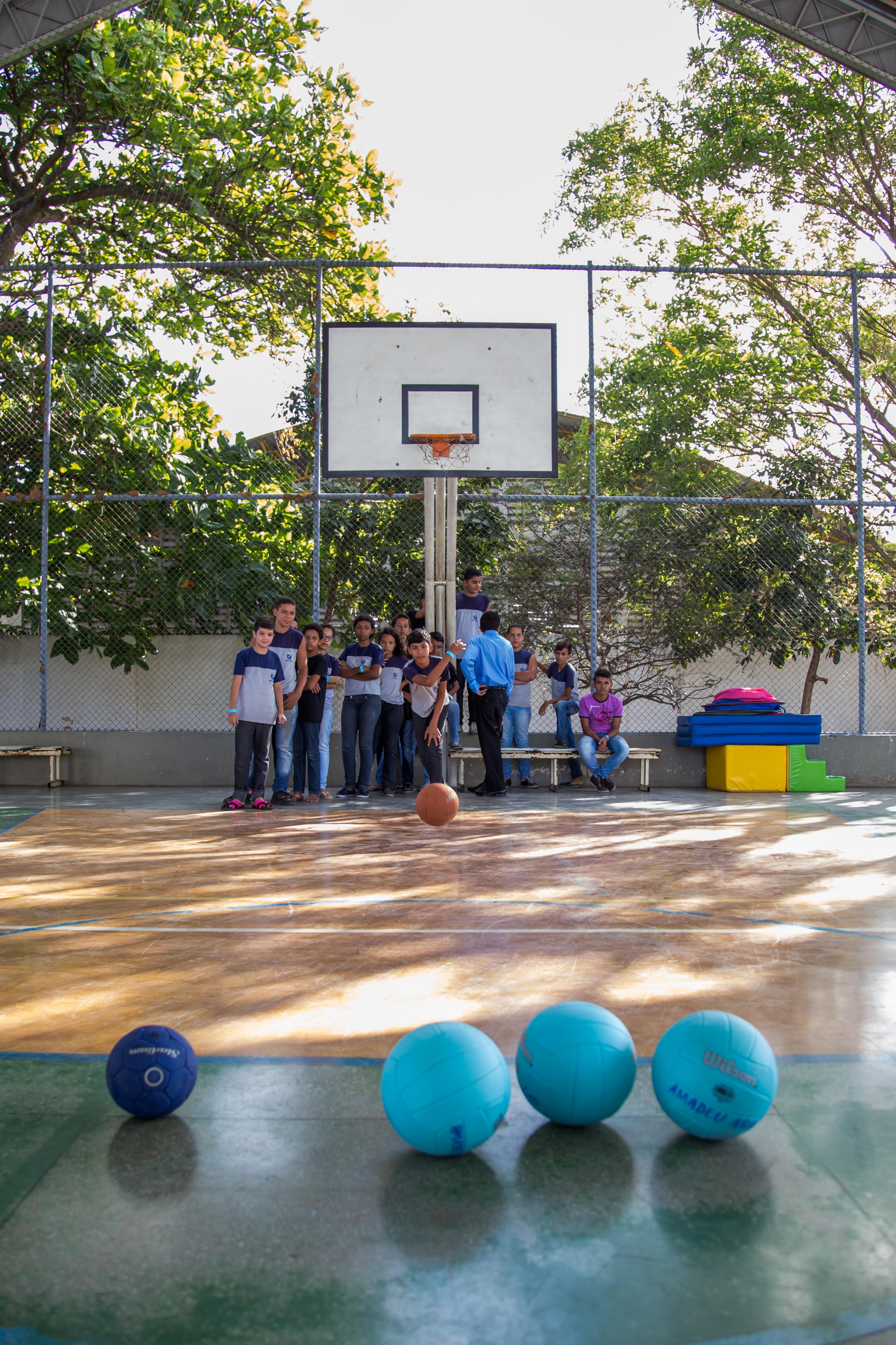Grupo de estudantes joga bilocha em uma quadra de esportes.