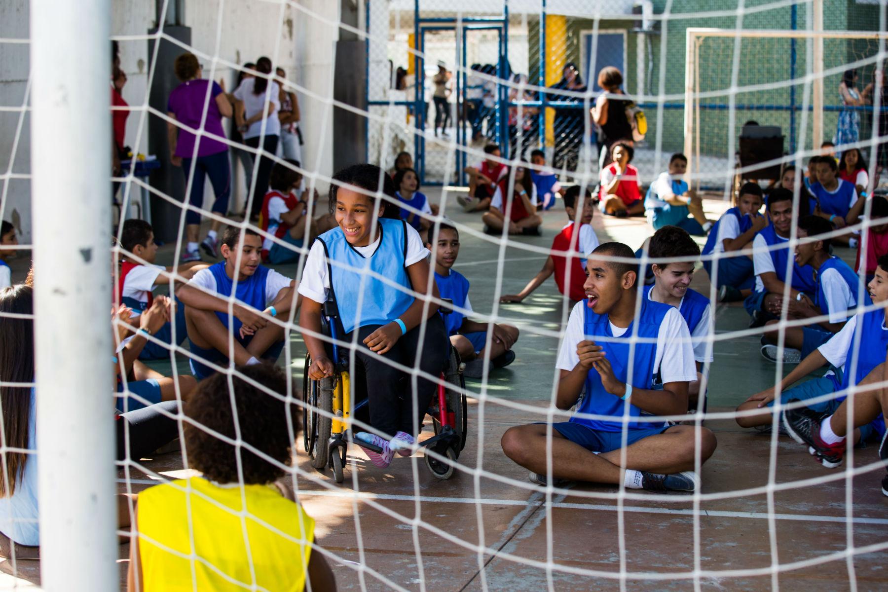 Estudantes realizam atividade em quadra esportiva. Os adolescentes estão sentados no chão. Uma garota em uma cadeira de rodas sorri no centro da cena.
