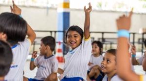 Crianças de 6 anos levantam as mãos e pulam em quadra escolar.