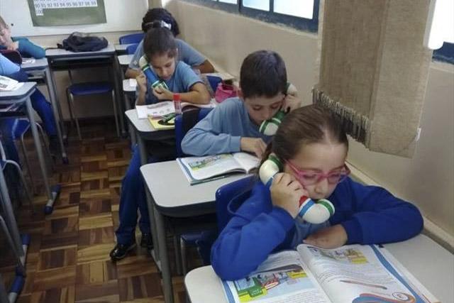 Estudantes sentados em carteira escolar leem livros em voz alta segurando um telefone de PVC