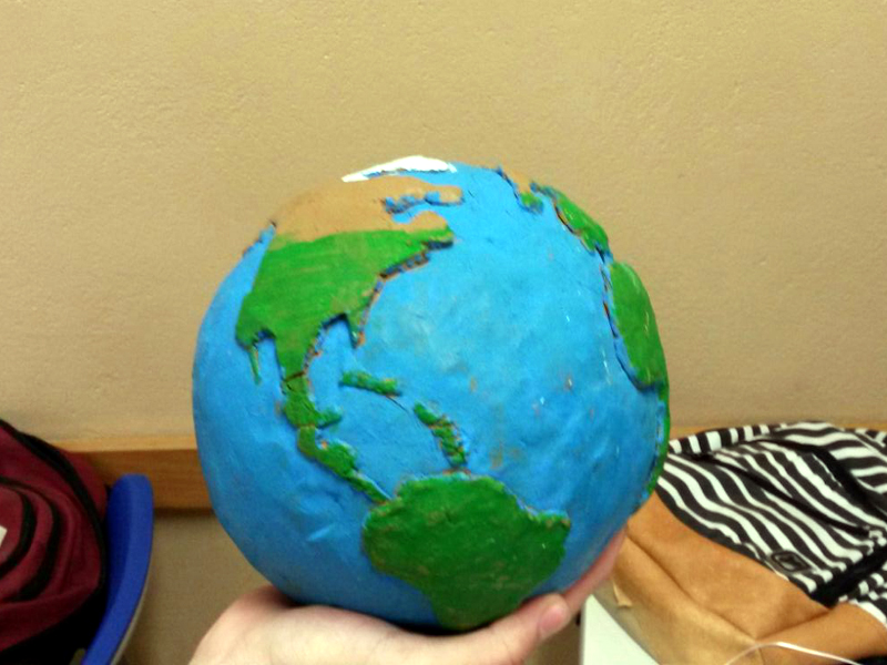 A foto mostra parcialmente a mão de uma pessoa que segura um globo terrestre feito com os continentes em alto relevo nas cores verdes e marrom e os oceanos na cor azul em baixo relevo.