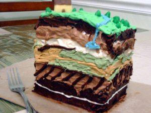 Bolo sobre um suporte de cor bege em cima da mesa ao lado de um garfo. O bolo apresenta diversas camadas de cores diferentes, cada uma representando uma camada do solo. A primeira camada é verde e representa a vegetação, há também pequenos arbustos em verde escuro sobre a camada verde, assim como um rio representado por um filete em azul que cruza a vegetação. A segunda camada, num marrom escuro, representa outra camada do solo. As cores se sucedem nas camadas representando a composição do solo nas cores marrom claro, bege, em seguida, uma alternância de verde claro e amarelo, de marrom escuro e claro e, na última camada, marrom escuro com uma linha que corta essa ultima camada em branco. A ideia das diferentes cores é representar as diversas camadas do solo.