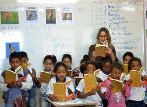 Grupo de cerca de dez crianças e uma mulher adulta seguram livros diante de si.
