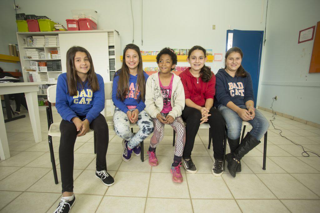 Quatro garotas estão sentadas lado a lado em cadeiras dentro de uma sala de aula. Elas sorriem.