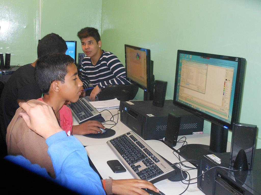 Estudante usam computadores na sala de informática para criar desenhos animados.