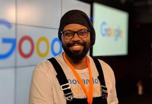 Foto de perfil de Doug sorrindo. Ele usa uma toca preta, uma camiseta branca sob um macacão escuro e óculos. Ele é negro e tem barba.