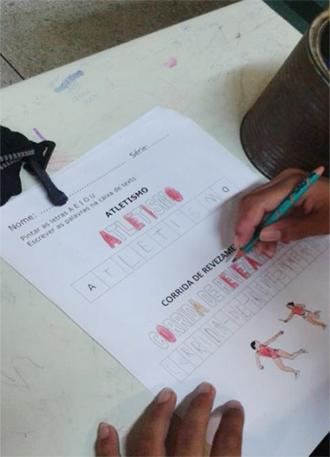 Estudante colore um desenho em uma folha sulfite. As figuras mostram pessoas praticando esportes e palavras relacionadas a atletismo.