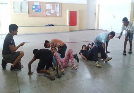 Dois estudantes seguram as pontas de uma corda e a sustentam a cerca de meio metro do chão. Um grupo de crianças passa por debaixo da corda.