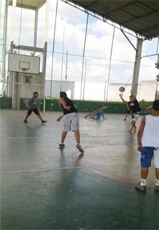 Um garoto arremessa uma bola em outro durante uma partida de queimada em uma quadra esportiva.