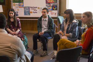 Um grupo de jovens está sentado em cadeiras, em formato de círculo, em uma sala escolar. Fim da descrição.