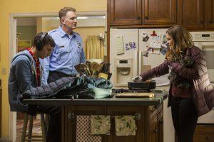 Sam, seu pai e sua mãe conversam na cozinha de casa.