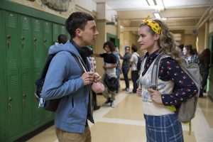 Sam conversa com uma colega no corredor da escola. Fim da descrição.