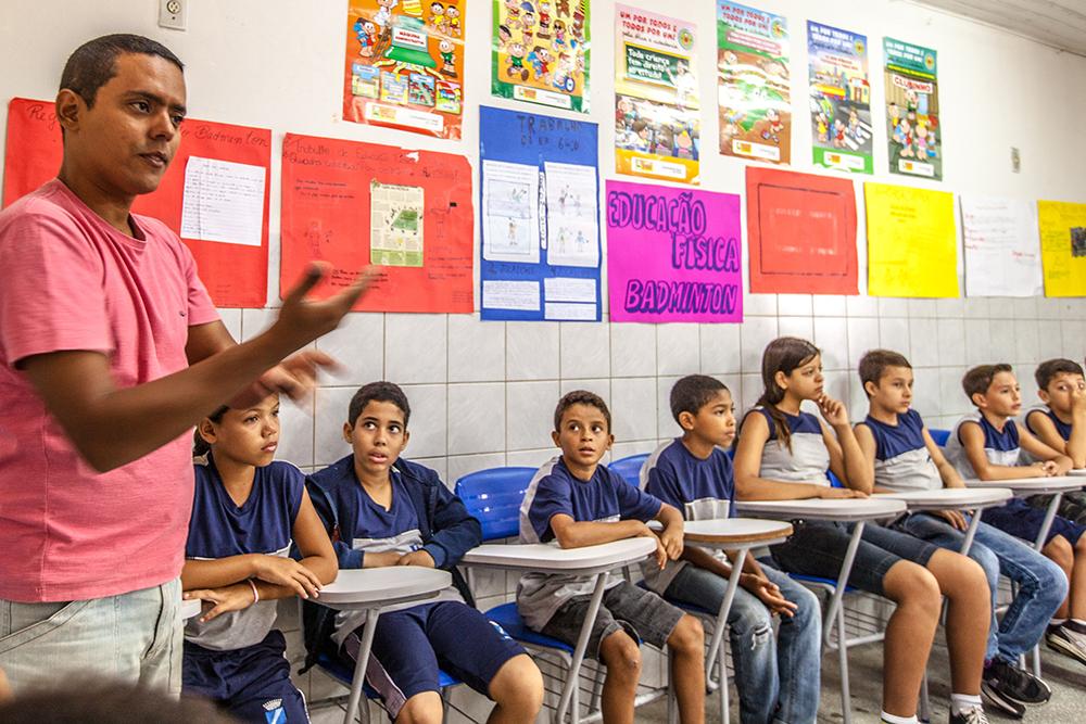 """Cerca de oito alunos do ensino fundamental estão sentados em sala de aula olhando para um professor. Na parede atrás dele há um cartaz escrito """"Educação física badminton""""."""