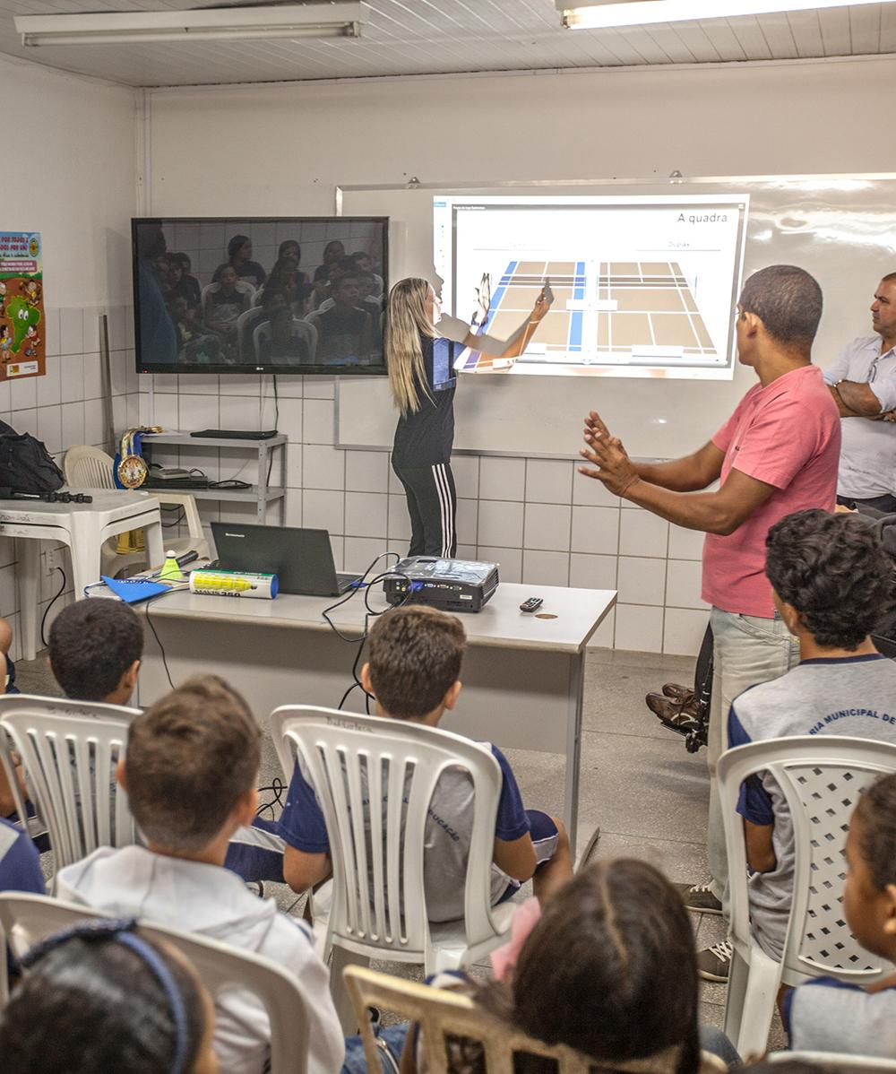 Alunos sentados em sala de aula olham para lousa, onde uma professora explica a matéria diante de uma projeção na lousa.