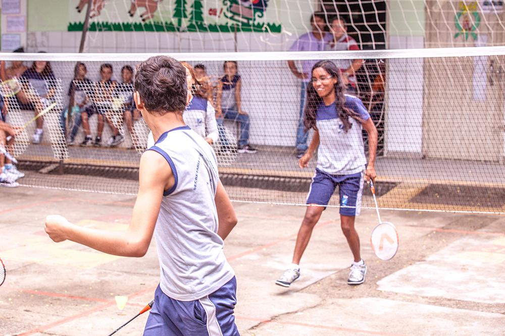 Um garoto e uma garota se enfrentam em uma partida de badminton na escola.