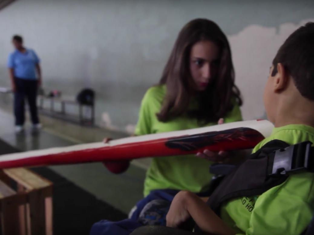Uma colega segura um pedaço de PVC cortado como calha para que Pedro direcione a jogada com o pescoço.