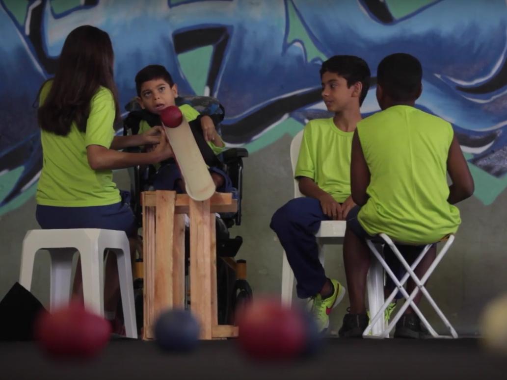 Com a calha apoiada em um caixote de madeira, Pedro se prepara para fazer o lançamento da bola com o pescoço. Sua colega de equipe segura a calha na altura do pescoço do garoto. Os outros dois jogadores ao lado assistem à jogada.