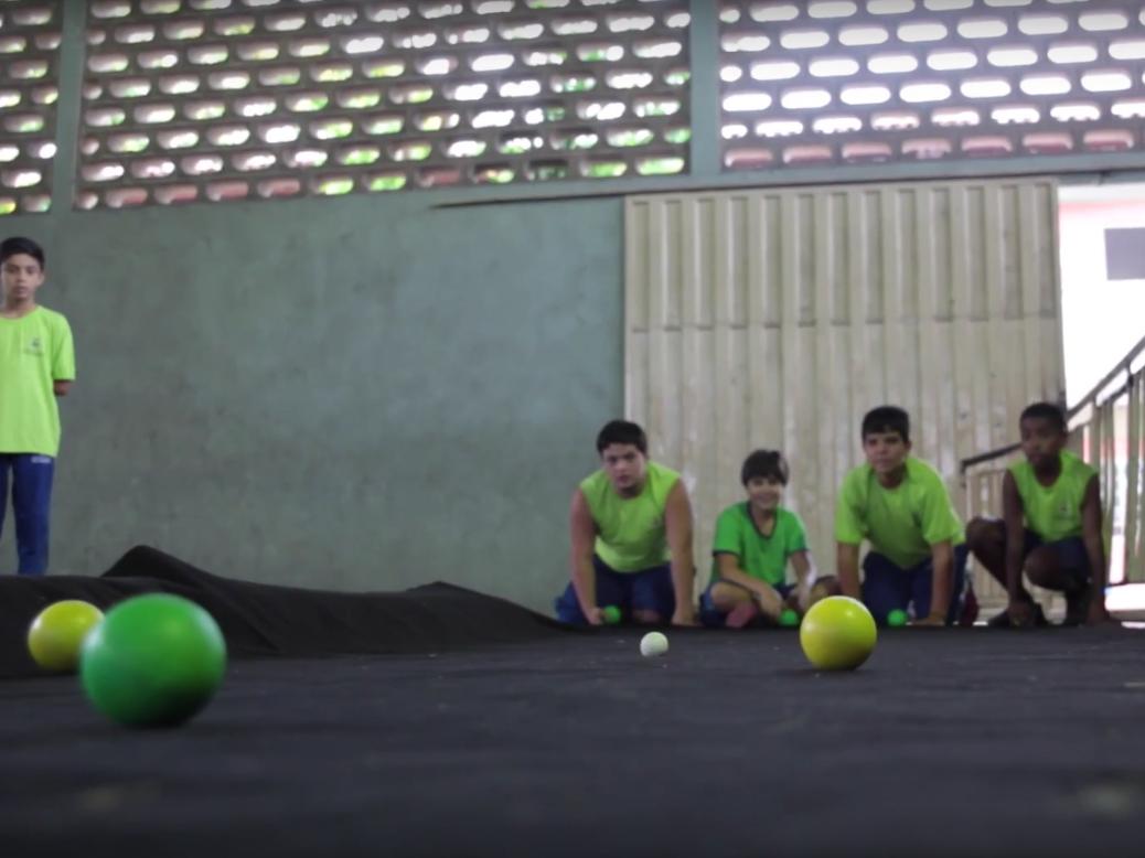 Três crianças ajoelhadas jogam as bolas de bocha em um tapete escuro.