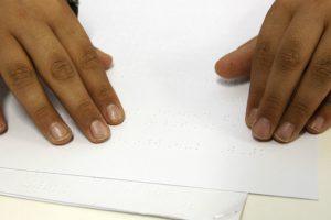 Duas mãos deslizam sobre superfície de folha com impressão braille.