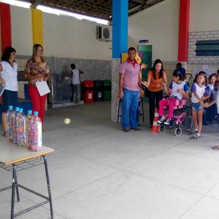 Um grupo de crianças forma fila para jogar boliche. Três professores observam a atividade.