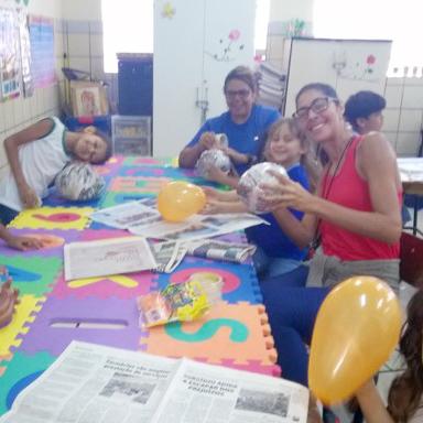 Duas professoras auxiliam duas alunas a confeccionar os brinquedos. Elas estão ao redor de uma mesa repleta de itens como papeis, tesoura, papéis coloridos, etc.
