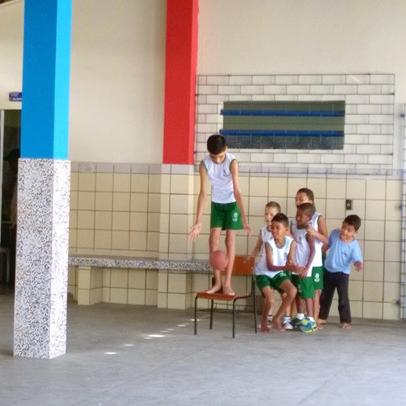 Garoto de pé em cima de uma cadeira no pátio da escola brinca de segurar uma bola com os joelhos. Seus colegas observam a atividade.