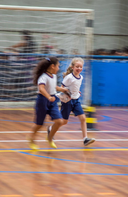 Duas garotas correm em uma quadra esportiva, lado a lado, cada uma segurando uma ponta de uma folha de jornal.