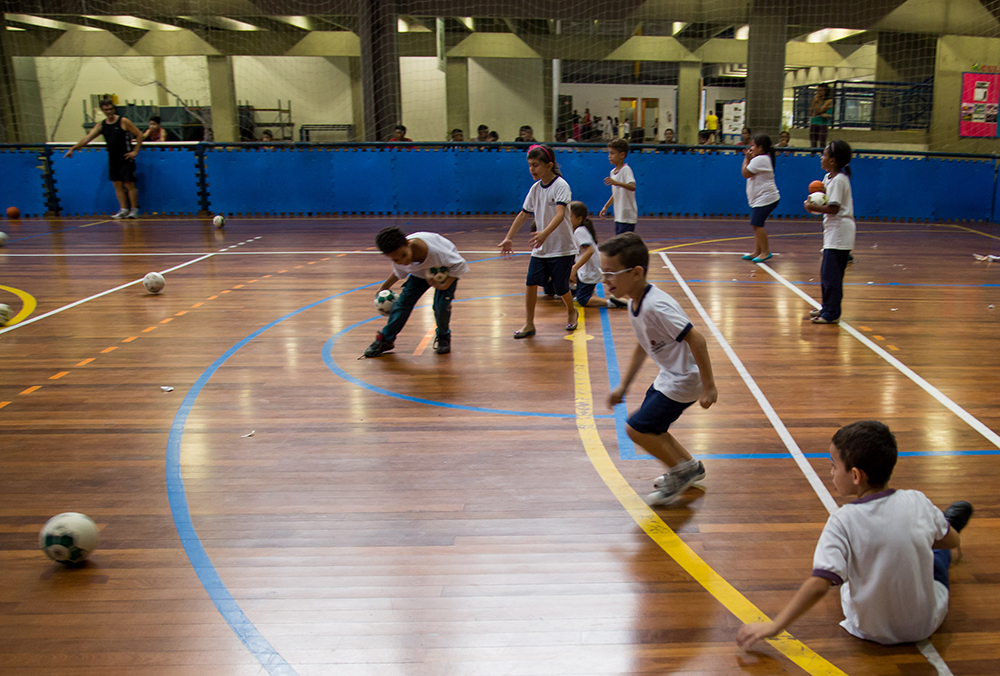 Estudantes em fila arremessam bolas de vôlei em uma bola de basquete colocada no centro da quadra.