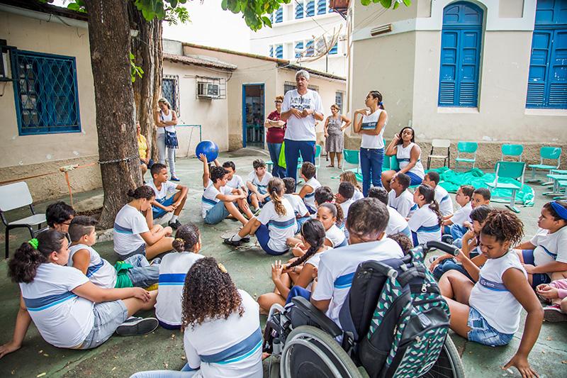 Várias crianças estão sentadas em um pátio de escola diante de um professor de educação física que fala algo.